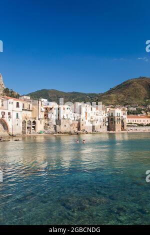 Cefalù, Palermo, Sicilia, Italia. Vista a través del tranquilo puerto hacia el casco antiguo, casas colgadas agrupadas a lo largo de la orilla del mar.