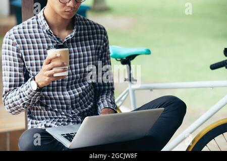 Imagen recortada de un desarrollador de software serio sentado en un banco en el parque, bebiendo café y trabajando en un nuevo gran proyecto