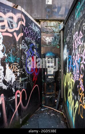 Un parquímetro descuidado en el centro de la ciudad de Liverpool rodeado de graffiti y basura.