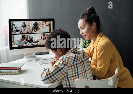 Madre ayudando a su hijo a hacer la tarea en la mesa durante la conversación en línea en la computadora