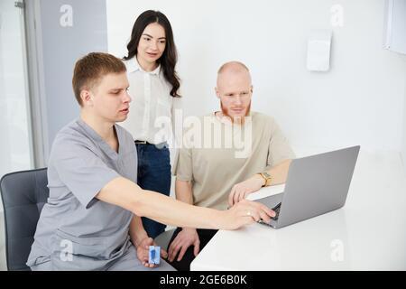 Un joven dentista consulta a dos pacientes.
