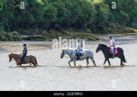 Jinetes en el río Gannel a marea baja en Newquay en Cornwall.