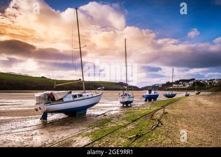 Luz nocturna sobre varios veleros amarrados en la costa del río Gannel en marea baja en Newquay en Cornwall.