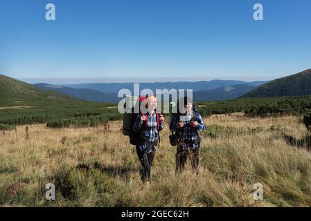 pareja de turistas enamorados hombre y mujer de pie en la llanura con mochilas detrás de sus espaldas. Espacio de copia