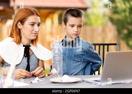 Mamá e hijo están haciendo experimentos físicos en casa. Experiencia con un niño sobre cómo colocar un huevo hervido en el cuello estrecho de una botella de plástico usi