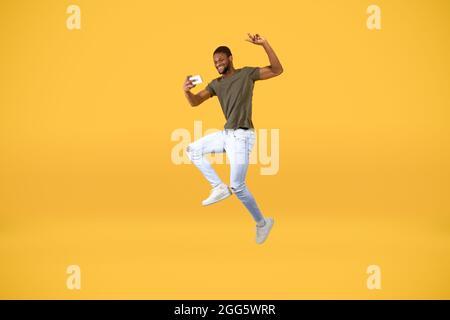 Loco africano americano hombre haciendo selfie en el smartphone mientras que salta en el aire sobre el fondo amarillo del estudio