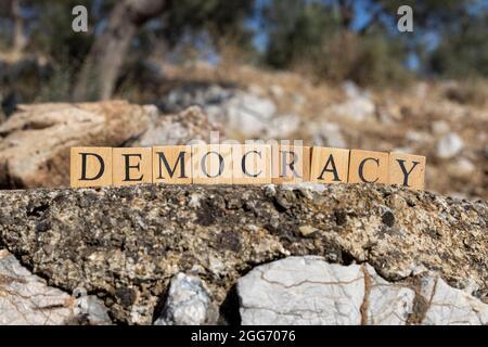 La palabra Democracia fue creada a partir de cubos de madera. Fotografiado en la pared. Primer plano.