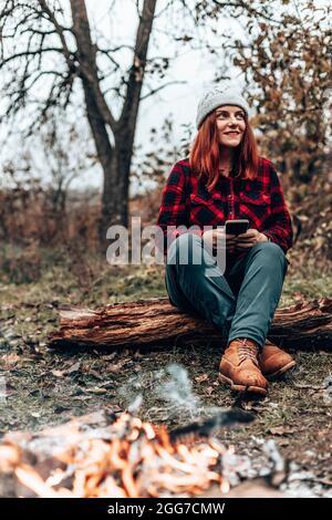 Una chica de viaje con ropa hipster se sienta en un tronco disfrutando, relajándose en el bosque cerca del fuego en camping. Mujer que utiliza el smartphone en la naturaleza