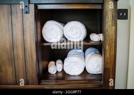 Las toallas blancas enrolladas se organizan en un armario para los huéspedes
