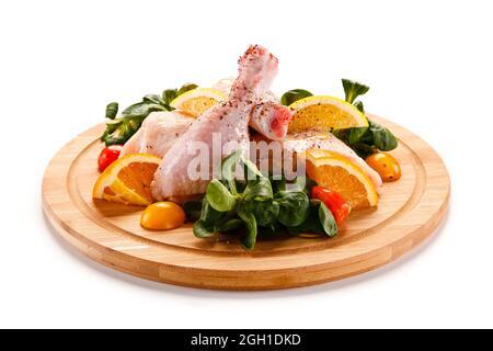 Chuletas de cerdo crudas en tabla de cortar y verduras.