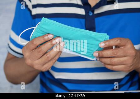 mano de hombre sosteniendo máscara facial quirúrgica, de cerca