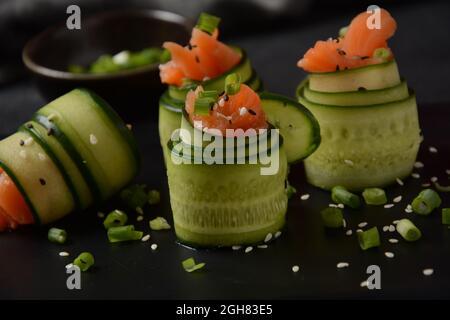 Rollos de pepino con trozos de salmón salado, semillas de sésamo blanco y negro, cebolla verde picada. Aperitivos vegetales de vacaciones