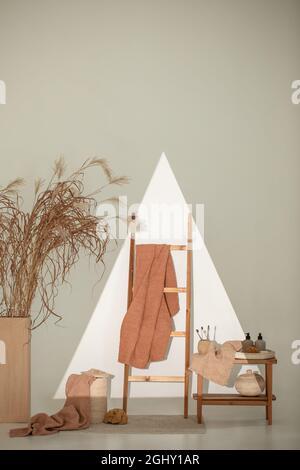 Toallas naturales de waffle en tonos tierra sobre banco de madera y escalera de toallas con cepillos de bambú, cestas de ratán y dispensador de jabón. Coche de cuerpo diario
