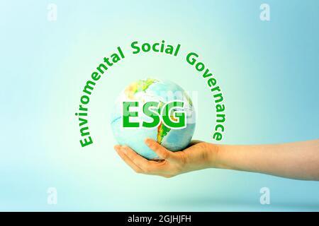 Modernización de la ESG Gobernanza social ambiental, conservación y política de RSE. Globo terráqueo en manos sobre fondo azul. Concepto de ecología y protección de la naturaleza. Fotografías de alta calidad