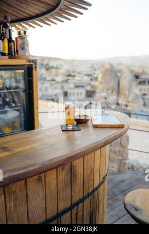 Una copa de cerveza fría con aperitivos y un menú en una barra redonda de madera en el bar