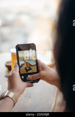 Recortar anónimo mujer tomando la foto con el teléfono móvil de cerveza y aperitivos en el bar