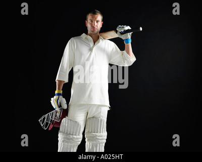 Jugador de cricket, de pie sosteniendo bate de críquet para llevar al hombro.