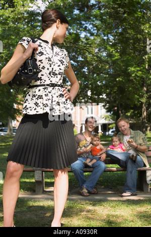 Mujer de pie delante de los hombres con hijos en Park