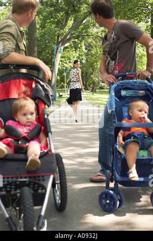 Los hombres con bebés en cochecitos mirando a la mujer Caminando