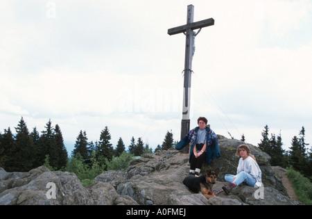 Cruz en la cima de la montaña Lusen, dos mujeres y un perro descansando, Alemania, Baviera, Parque Nacional Bosque Bávaro