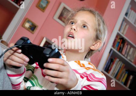 Niña jugando juego de ordenador en la consola Sony Playstation, Inglaterra, Reino Unido.