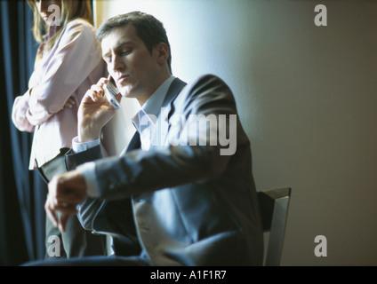 Empresario en el teléfono, el tiempo de revisión, mujer de pie junto a él