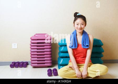 Retrato de una adolescente sentado delante de la pila de aeróbicos pasos