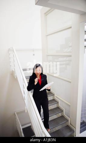 Un alto ángulo de visualización de una empresaria sosteniendo un periódico y bajando una escalera