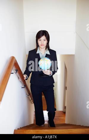 Retrato de una empresaria sosteniendo un globo y caminar sobre la escalera