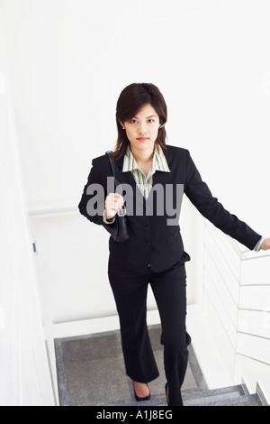 Retrato de una empresaria subiendo por una escalera