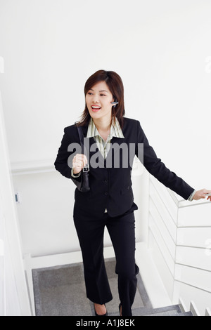 Un alto ángulo de visualización de una empresaria subiendo por una escalera y sonriente