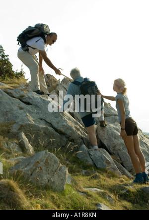 Excursionistas subiendo por las rocas, el hombre y la niña ayudando a mujer madura