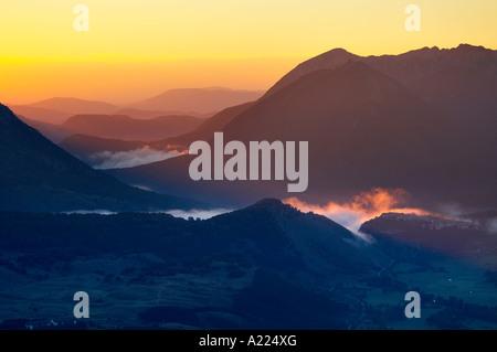 Mist arremolinándose alrededor de la aldea de Opi recogido por un eje de la luz del amanecer, el Parque Nacional Foto de stock