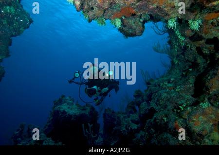 Una mujer fotógrafo mira hacia una caverna en un arrecife en Pequeño Caimán
