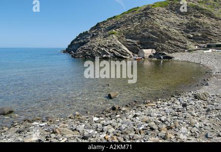 Playa de guijarros con solitaria cabaña de pesca en la bahía de Cala dels Alocs Foto de stock