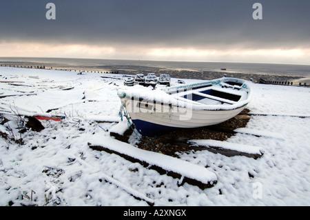 Nieve en un barco pesquero solitario en Worthing Beach después de las tormentas de invierno en Sussex y Kent en el sur de Inglaterra