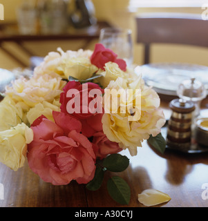 Cortar rosado y crema rose cabezas en la mesa de comedor de madera