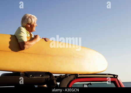 El perfil lateral de un hombre maduro, sentado en un vehículo utilitario deportivo y sosteniendo una tabla de surf