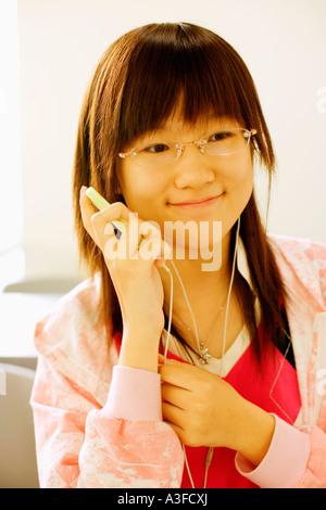 Close-up de una adolescente para escuchar un reproductor de MP3 en el aula Foto de stock