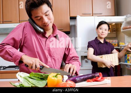 Cerca de una mitad hombre adulto cortar verduras mientras habla por un teléfono inalámbrico y una joven mirándolo