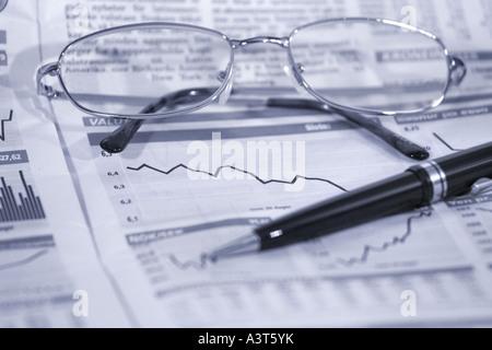 Gafas y bolígrafo encima de cifras financieras con el precio de las acciones