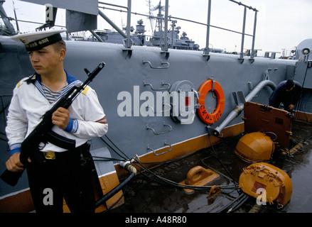 Federación de marinero con AK 47 en guardia en la cubierta del buque de guerra en los muelles en Sebastopol Foto de stock