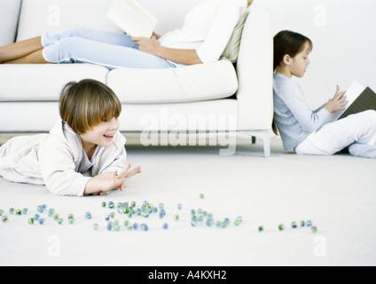 Niño jugando canicas en el suelo, la mujer y la niña leyendo en segundo plano.
