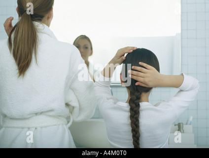 Mujer y niña cabello fijación, vista trasera Foto de stock