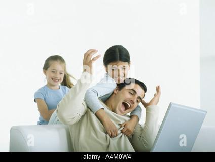 Dos niñas detrás de hombre sentado con laptop, uno con los brazos alrededor de él