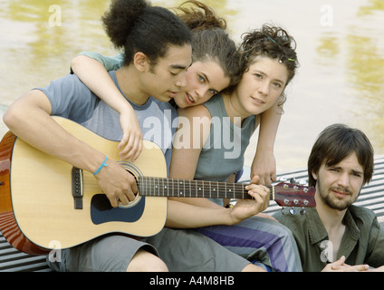 Cuatro jóvenes amigos reunidos alrededor de guitarra