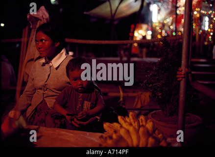 Camboya Phnom Penh madre e hijo sentarse a vendedores de fruta a lo largo de Sisowath Quay por Tonl Sap River en Foto de stock