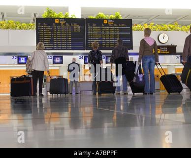 Salidas de pasajeros aeropuerto pasajeros esperando en el pasillo mirando pantallas de información de vuelos de salida en la moderna terminal del aeropuerto