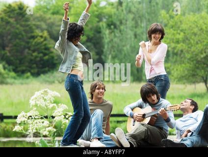 Grupo de amigos en el exterior, jóvenes mujeres bailando mientras toca la guitarra joven