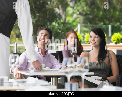Camarero trayendo café para pareja en el café al aire libre
